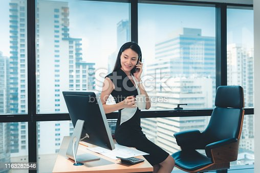 Portrait of Business Woman is Talking on Mobile Phone in Her Office., Beautiful of  Asian Woman is Calling to Someone on Her Cell Phone While Drinking a Cup of Coffee at Her Table Desktop.