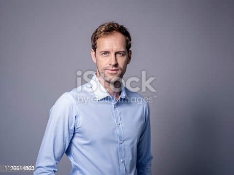 Portrait of handsome businessman against gray background. Male professional is wearing shirt. He is with blue eyes.
