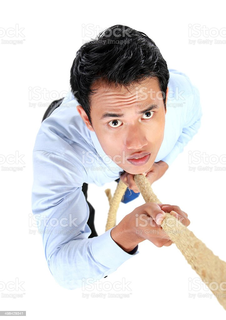 Portrait of businessman climb using rope stock photo