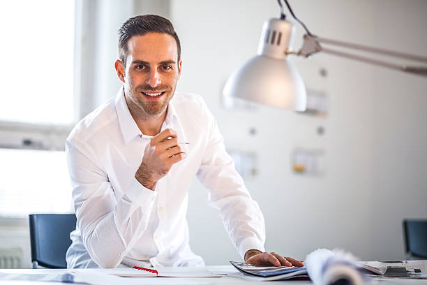 Portrait of businessman holding pen at desk in office – Foto