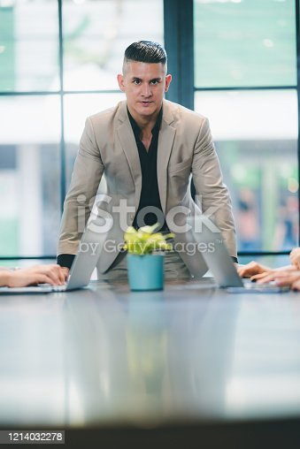 891418990 istock photo portrait of businessman in co-working space, handsome CEO smiling in suit 1214032278