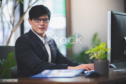 891418990 istock photo portrait of businessman in co-working space, handsome CEO smiling in suit 1214032295