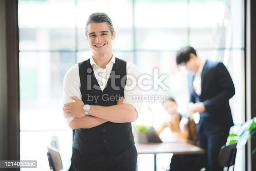 891418990 istock photo portrait of businessman in co-working space, handsome CEO smiling in suit 1214032350