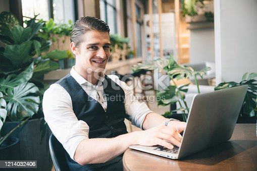 891418990 istock photo portrait of businessman in co-working space, handsome CEO smiling in suit 1214032406