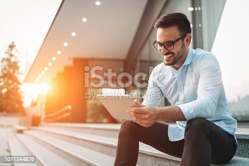 Portrait of businessman in glasses holding tablet outdoors