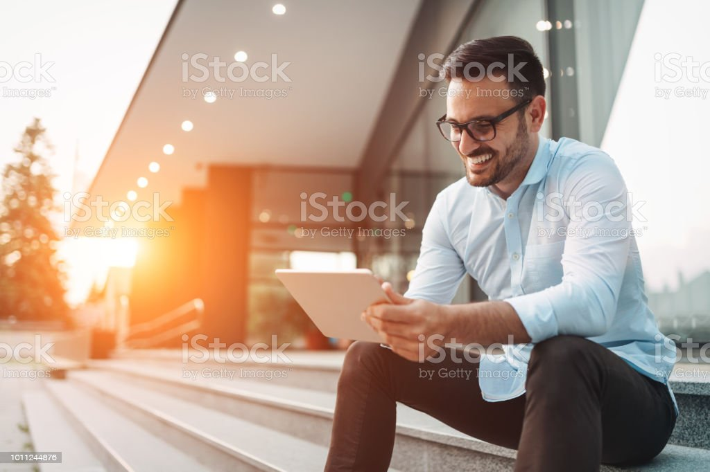 Portrait of businessman in glasses holding tablet stock photo