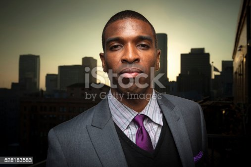 Portrait of a serious-looking African-American businessman standing in front of the Los Angeles Downtown skyline, silhouetted by sunset.