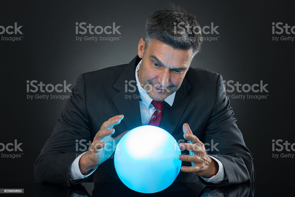 Portrait Of Businessman Predicting Future With Crystal Ball - foto de stock