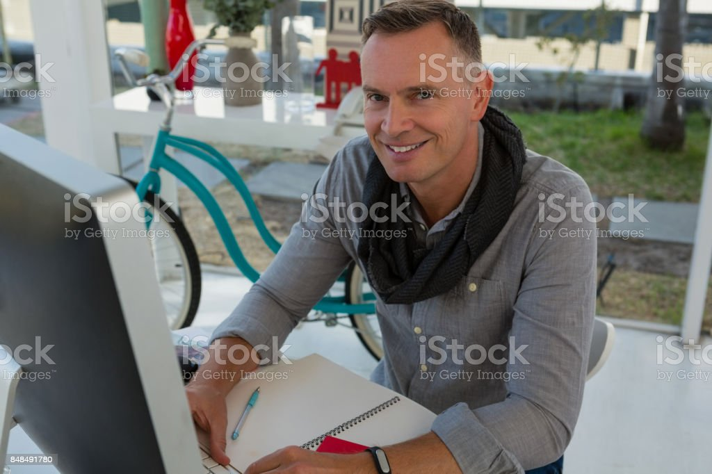 Portrait of businessman sitting at desk in office stock photo
