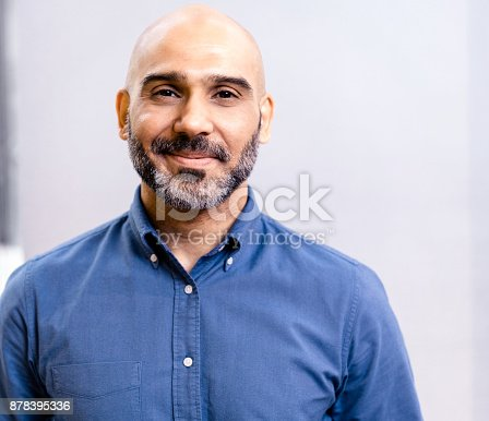 istock Portrait of businessman smiling against wall 878395336