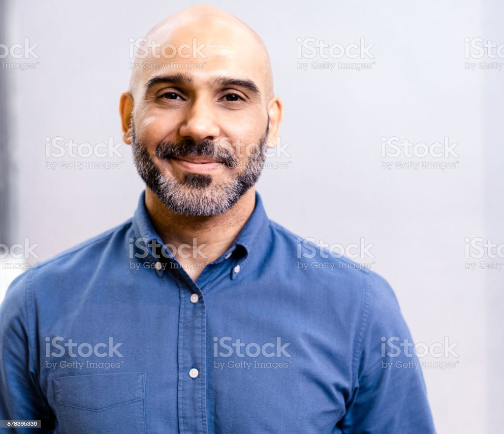 Portrait of businessman smiling against wall stock photo