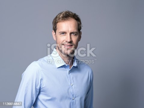 Portrait of businessman smiling over gray background. Confident mid adult executive is wearing shirt. Handsome male is with blue eyes.