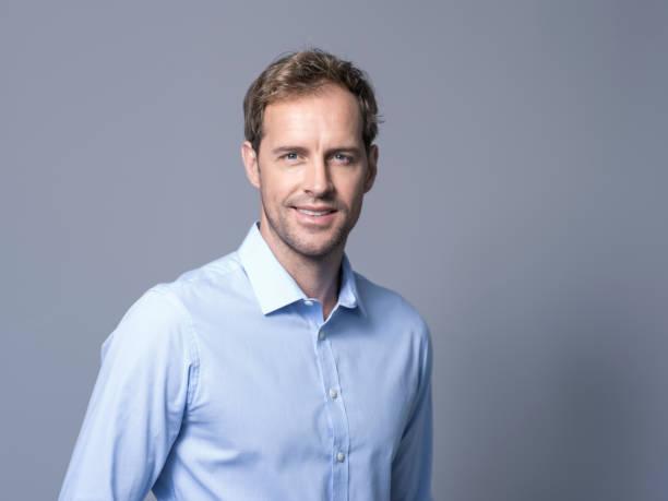 ritratto di uomo d'affari sorridente su sfondo grigio - man portrait foto e immagini stock