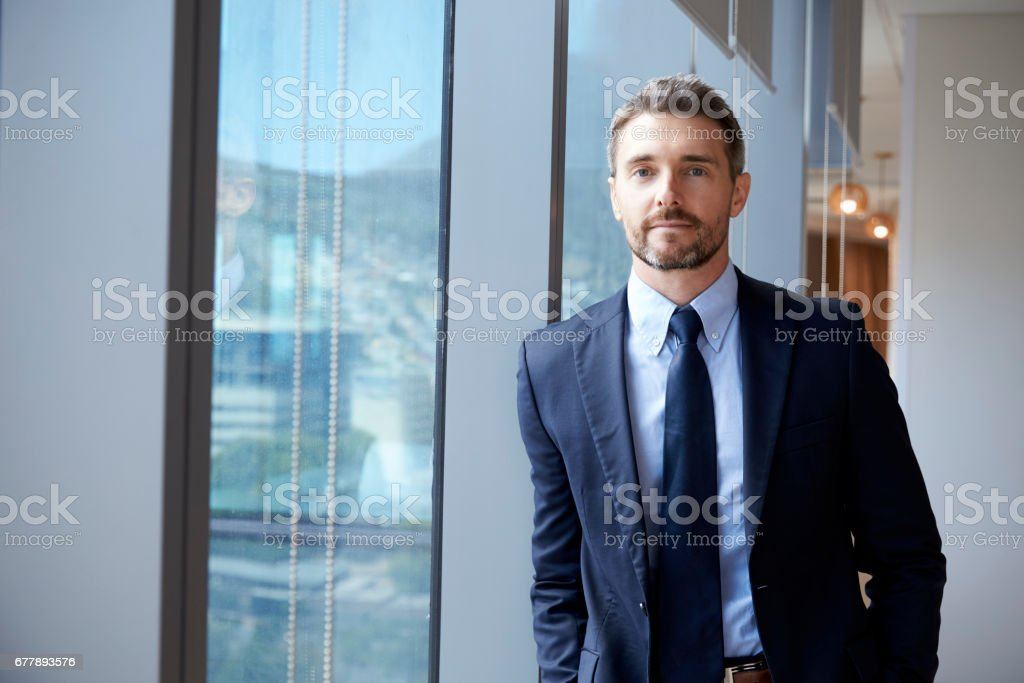 Portrait Of Businessman Standing By Window In Office stock photo