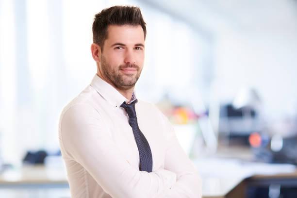 Porträt des Geschäftsmannes, der im Büro steht, während er lächelt und auf die Kamera schaut – Foto