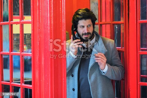 Portrait Of Businessman Talking At Telephone Booth, London