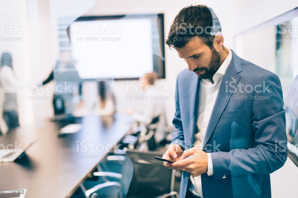 Portrait of businessman using phone in office zbiór zdjęć royalty-free