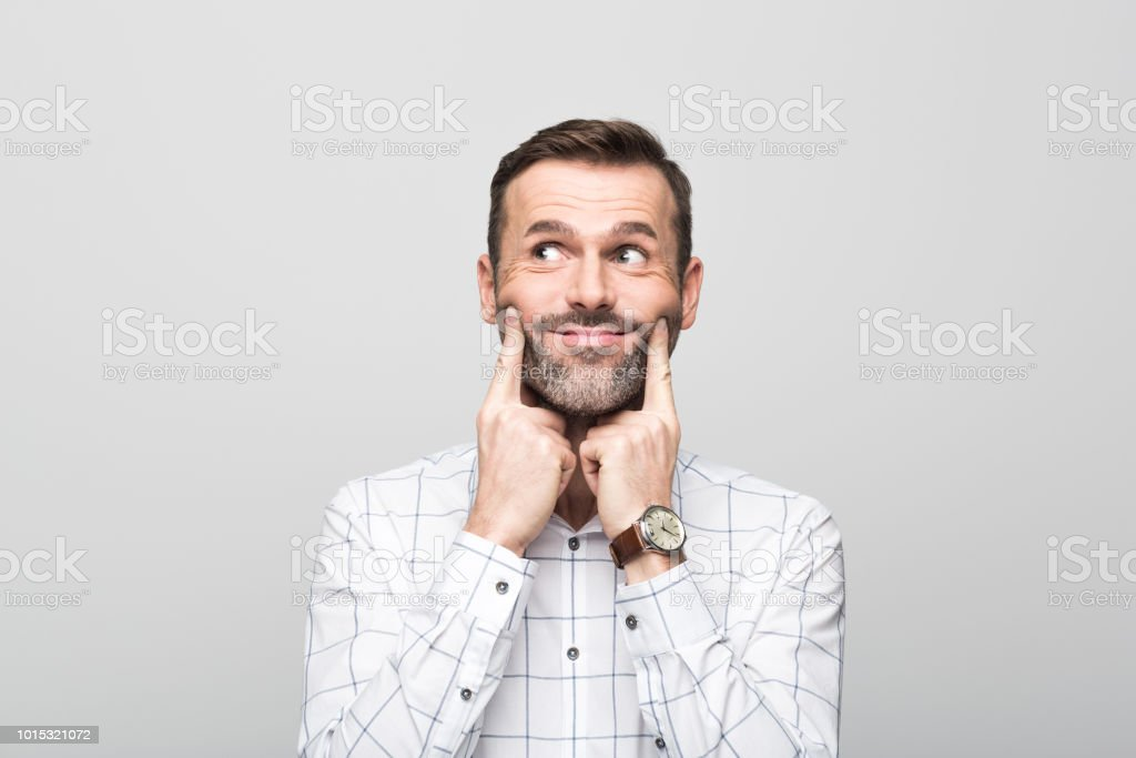 Portrait of businessman with fake smile, grey background Businessman looking away and making fake smile with index fingers. Studio shot, grey background. 30-39 Years Stock Photo
