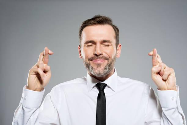 Portrait of businessman with fingers crossed, studio shot stock photo