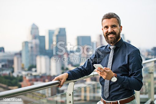 A portrait of businessman with smartphone standing against London rooftop view panorama. Copy space.