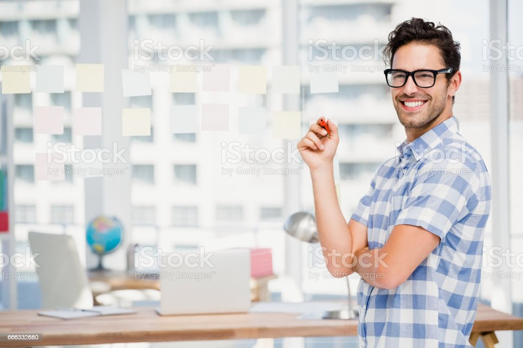 Portrait of businessman writing on sticky notes in office stock photo