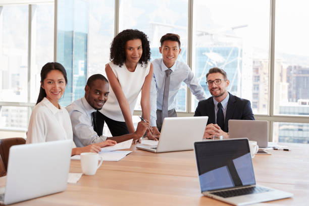Portrait Of Businesspeople Meeting Around Table In Office stock photo