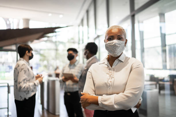 portrait of businesswoman at work with face mask - business stock pictures, royalty-free photos & images