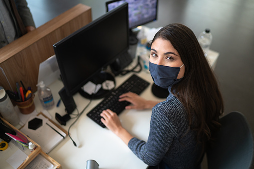Portrait of businesswoman / receptionist working wearing face mask