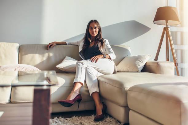 portret van zakenvrouw zittend op de bank ontspannen na het werk thuis - woman very rich stockfoto's en -beelden