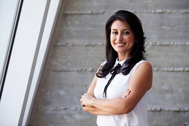 portrait of businesswoman standing against wall in office - mid volwassen vrouw stockfoto's en -beelden