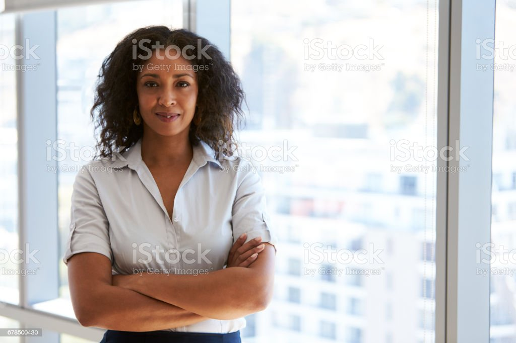 Portrait Of Businesswoman Standing By Window In Office stock photo