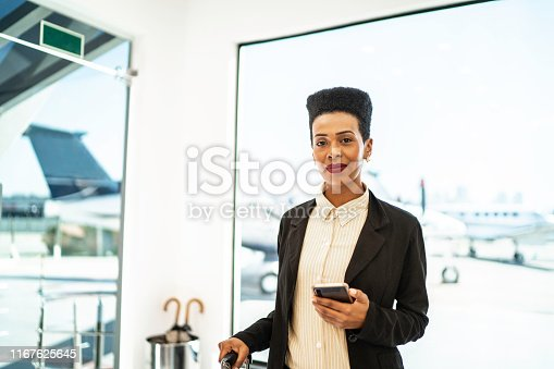 Portrait of businesswoman using cellphone inside an airport VIP lounge