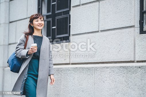 A businesswoman is walking in the street while holding a coffee cup.