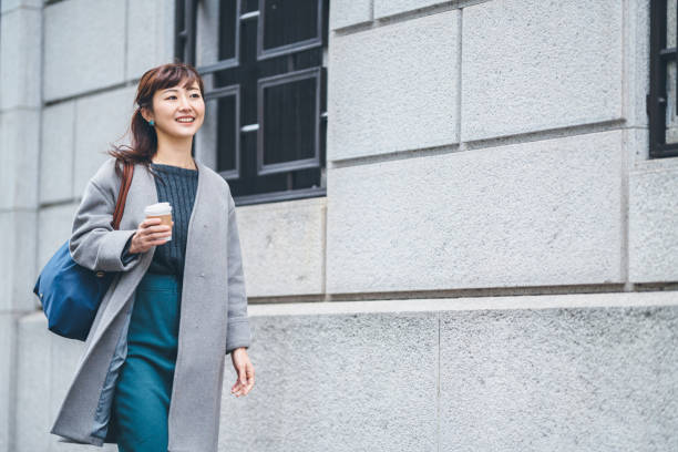 Portrait of businesswoman walking in street while holding coffee A businesswoman is walking in the street while holding a coffee cup. japanese ethnicity stock pictures, royalty-free photos & images