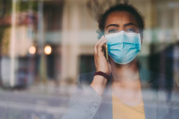 Portrait of businesswoman wearing protective face mask, COVID-19 pandemic stock photo