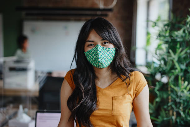 Portrait of businesswoman with cloth face mask after returning back to work stock photo