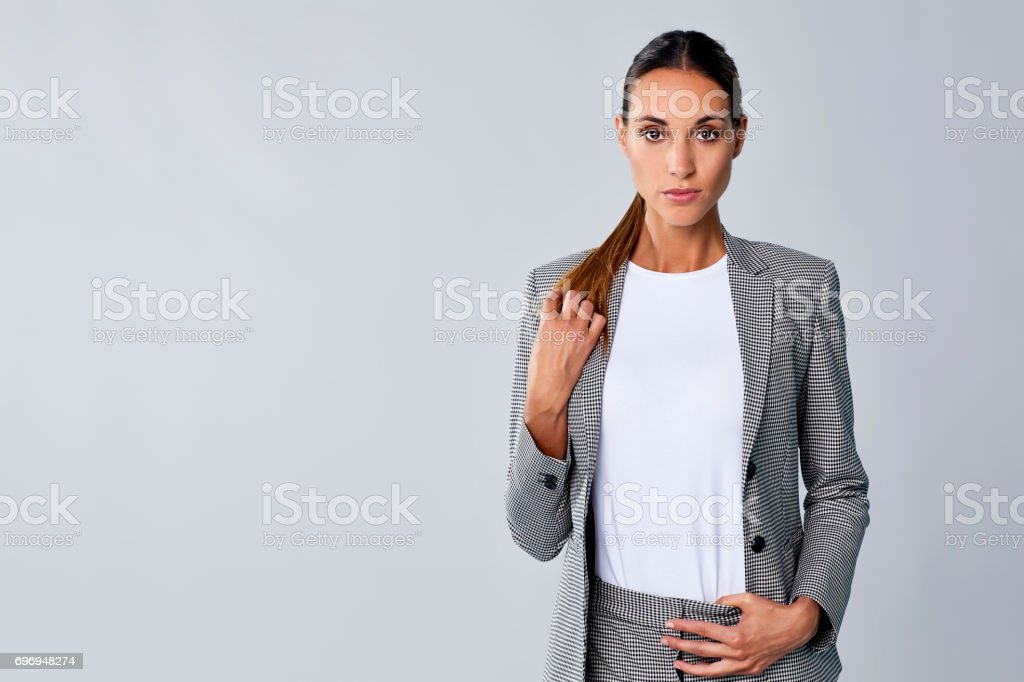 Portrait of businesswoman with hand in ponytail stock photo