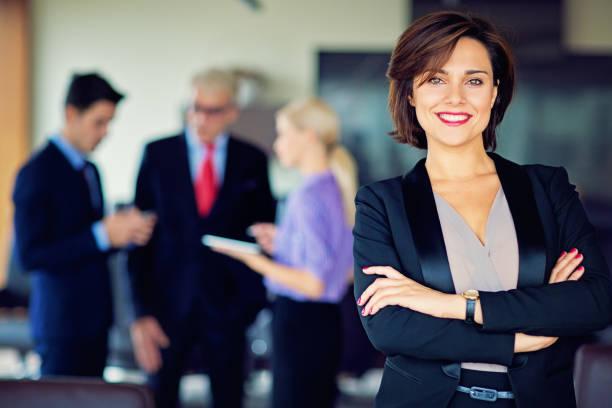 Retrato de mulher de negócios com a sua equipa - foto de acervo