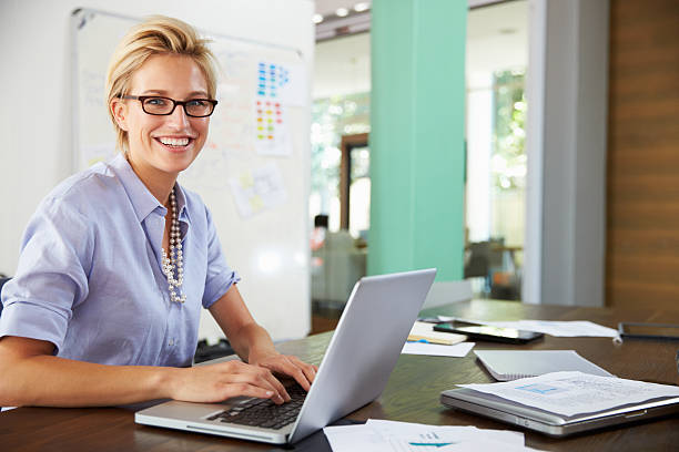 portrait of businesswoman working in creative office - white collar worker stock photos and pictures