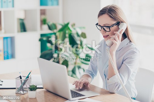 istock Portrait of busy, cheerful, attractive, pretty operator with hairstyle holding handset near ear, speaking on phone, checking information on pc, sitting in work place, station at desktop on chair 962402770