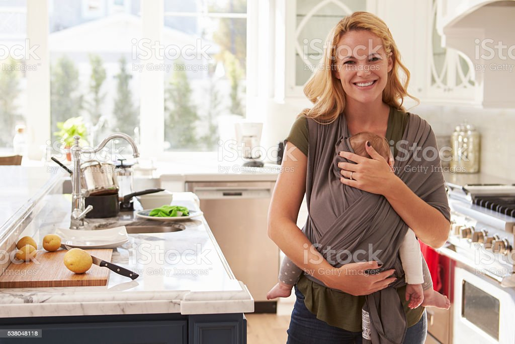 Portrait Of Busy Mother With Baby In Sling At Home stock photo
