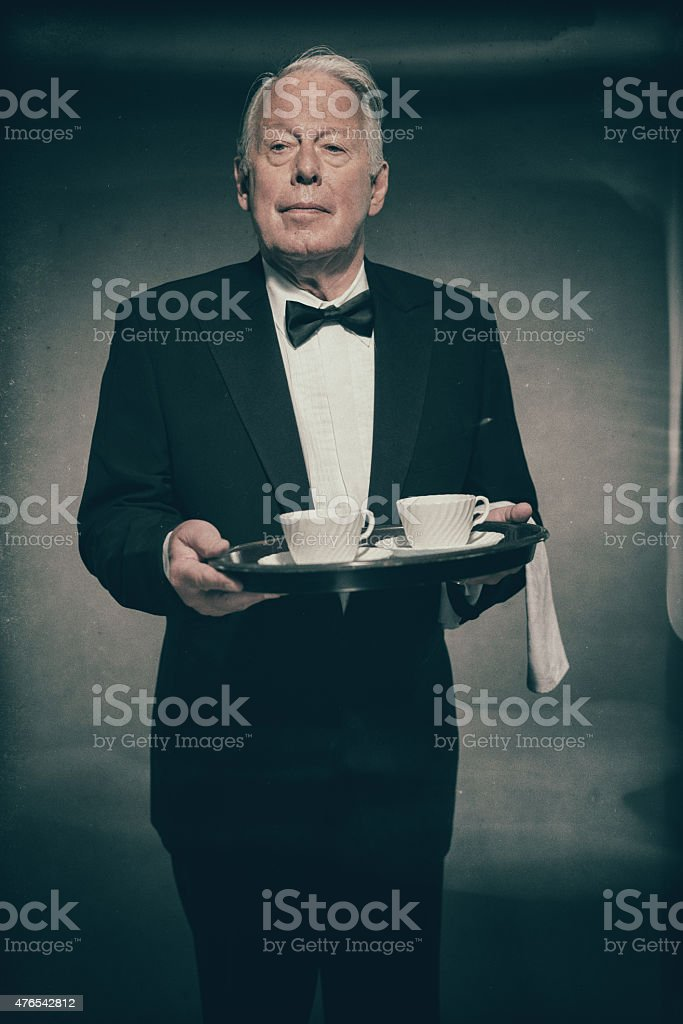 Portrait of Butler Holdig Tray of White Tea Cups stock photo