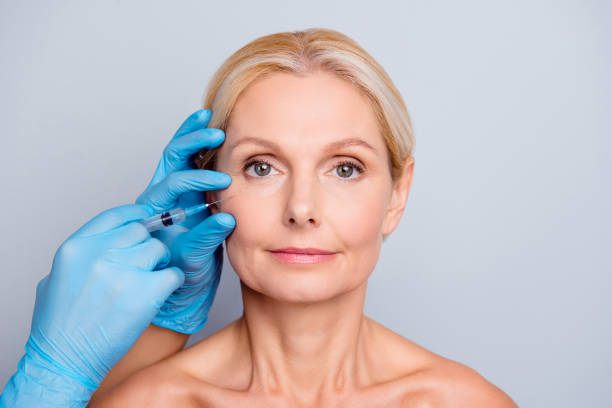 Portrait of calm serious charming aged woman with wrinkle getting injection in cheek in professional clinic hands in gloves making face contouring isolated on grey background Portrait of calm serious charming aged woman with wrinkle getting injection in cheek in professional clinic hands in gloves making face contouring isolated on grey background tighten stock pictures, royalty-free photos & images