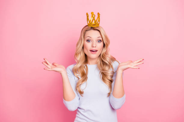portrait of carefree funky girl with gold crown on her head gesturing with palms looking at camera demonstrate her greatness isolated on pink background - stupidblonde stock pictures, royalty-free photos & images
