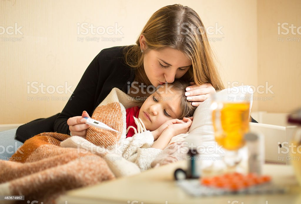 Portrait of caring mother kissing sick daughter in head stock photo