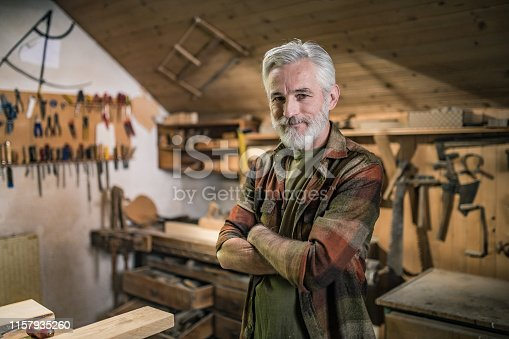 Portrait of smiling senior carpenter with arms crossed standing in workshop.
