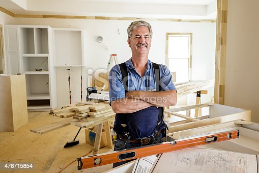 Portrait of trim carpenter inside home with kitchen cabinets and trim molding in the background. Carpenter age is in his 50s wearing eyeglasses and standing next to blueprints.