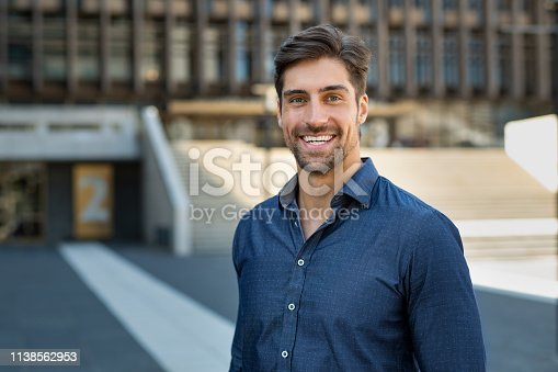 istock Portrait of casual smiling man 1138562953