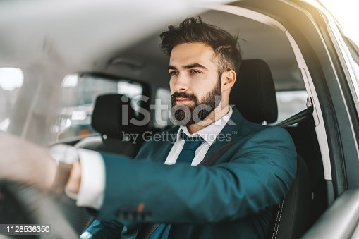Portrait of caucasian bearded businessman in formal wear driving car.