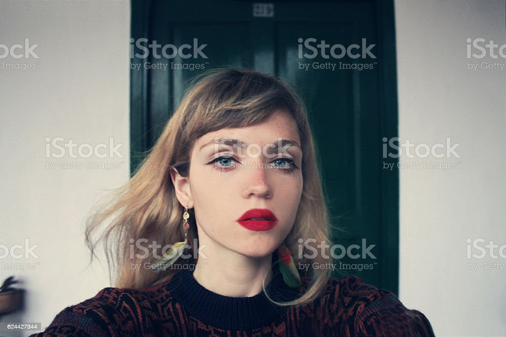 Portrait of caucasian blond female on background of wooden doors stock photo